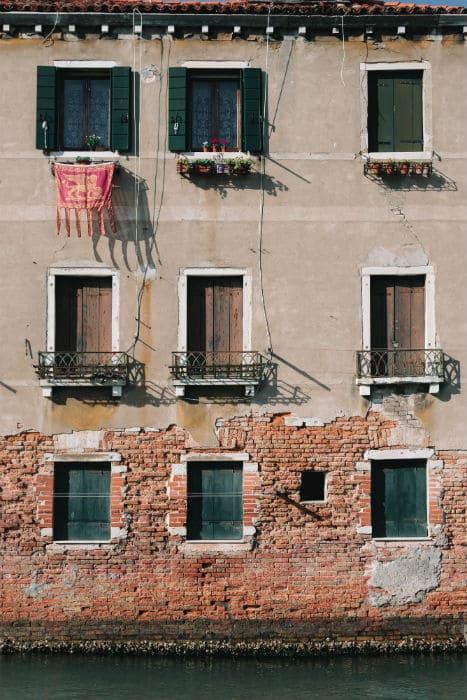 Fachada de um prédio com tijolo à vista na beira de um canal, com a bandeira da República de Veneza em uma janela, em Treviso, na Itália