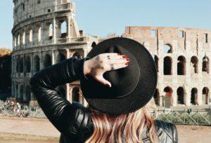 Mulher de costas, com a mão segurando seu chapéu, de frente ao Coliseu, em Roma, na Itália