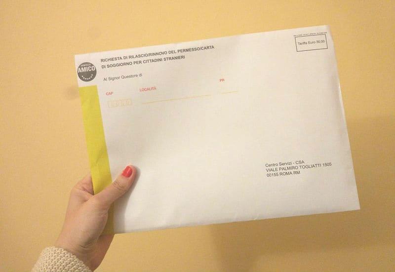 Mão segurando envelope do kit giallo, do permesso di soggiorno