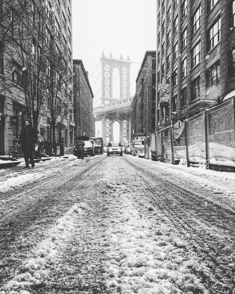 Foto em preto e branco de Nova York no inverno, com neve e a ponte do Brooklyn ao fundo