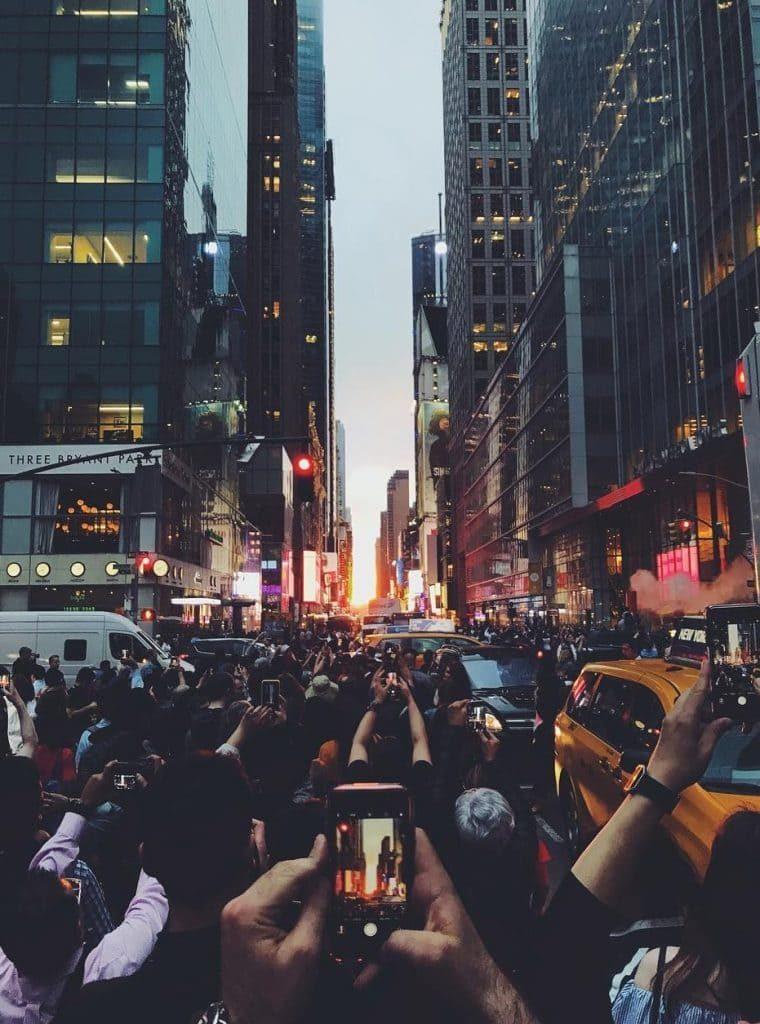Foto de uma rua lotada em Nova York, no por do sol, com muitos celulares tirando fotos ao mesmo tempo