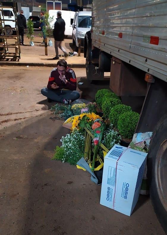 Homem sentado ao fundo, ao lado de um caminhão na Feira de Flores do CEAGESP, com flores e plantas no chão à sua frente