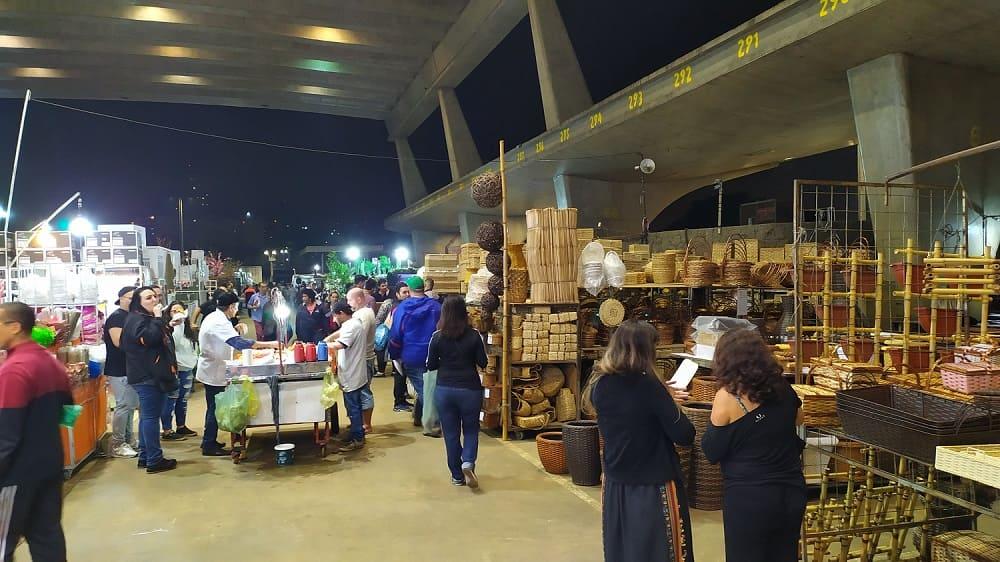 Feira de Flores do CEAGESP, com um carrinho no centro onde se vendem café e, dos lados, prateleiras com vasos e objetos de paisagismo