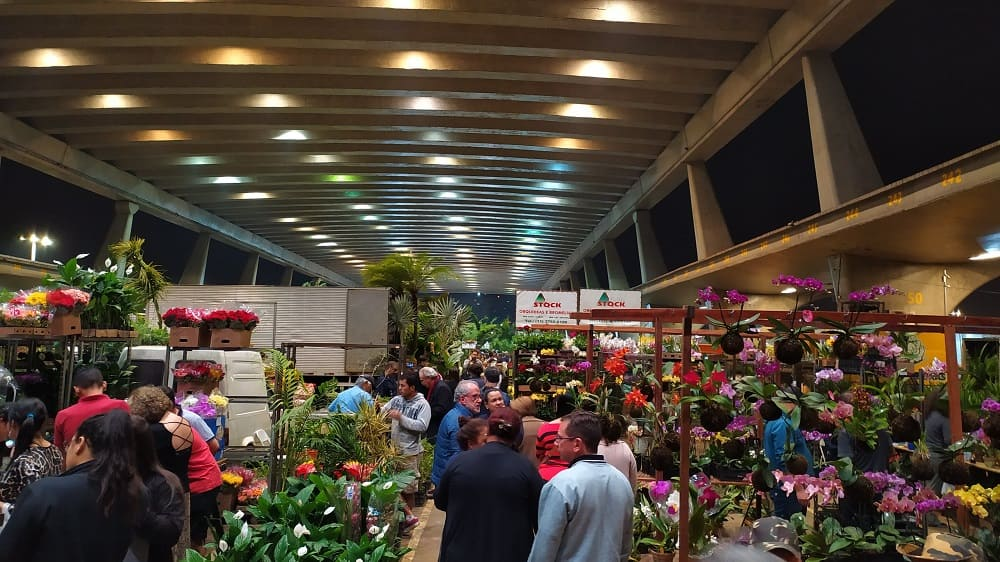 Foto da Feira de Flores do CEAGESP: um galpão comprido, com flores aos lados e muitas pessoas passando no centro