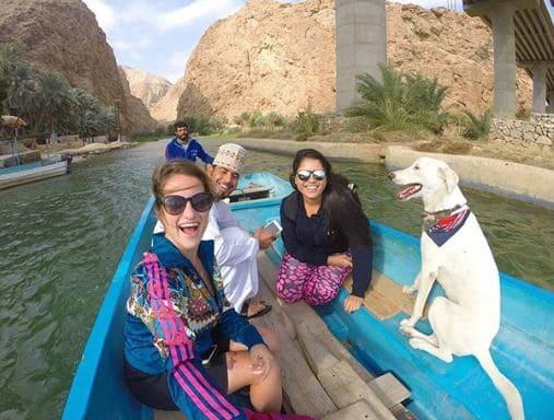 Duas mulheres, dois homens e um cachorro em um barco em Wadi Shab, no Omã