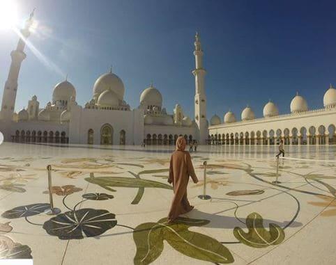 Mulher de costas caminhando na Grande Mesquita em Abu Dhabi