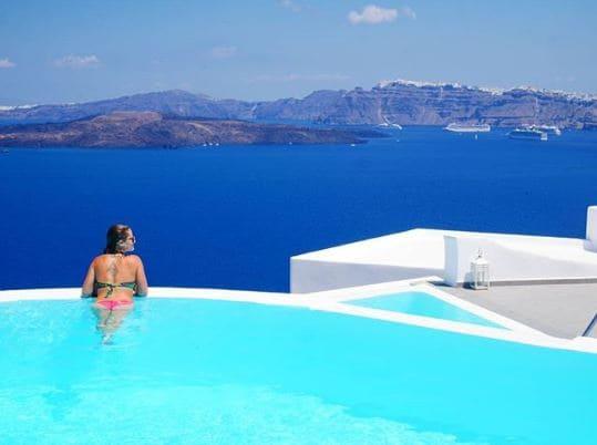 Mulher de costas, na beira da piscina, com vista para o mar em Santorini, na Grécia