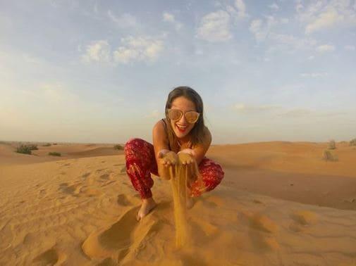 Mulher no deserto em Dubai, agachada, segurando um punhado de areia