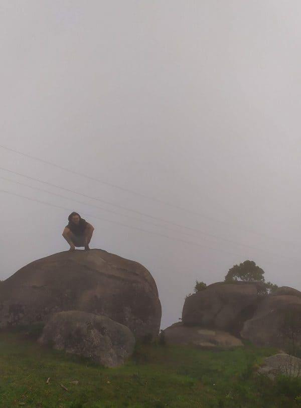 Foto no topo da Pedra da Macela, com homem em cima de uma pedra e muita neblina