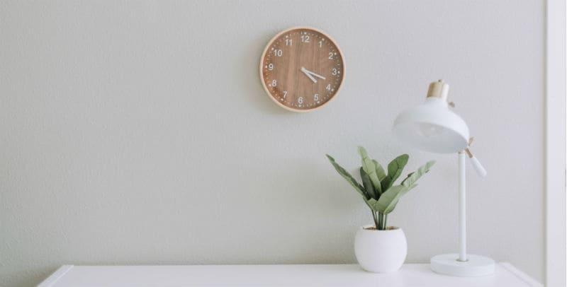 Parede branca com um relógio, um vaso de plantas e uma luminária sobre uma mesa, capa do texto sobre o que fazer na quarentena