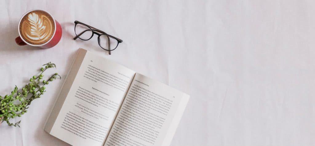 Sobre um tecido branco, se vêem um cappuccino, um ramo de folhinhas, um óculos e um livro aberto. O que fazer na quarentena pra passar o tempo
