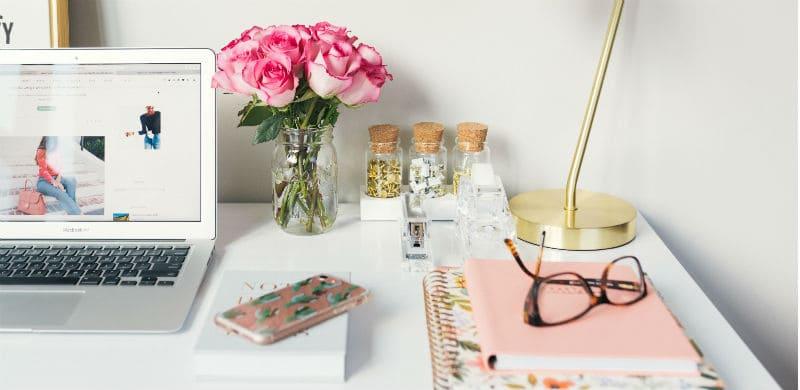 Imagem de um home office, com um computador, um pote com flores, cadernos e um óculos. Estudar na quarentena