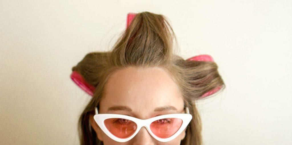 Mulher com bobes na cabeça e óculos cor de rosa. Autocuidado na quarentena