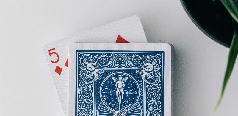 Baralho visto de cima, com um cinco de ouros virado embaixo das outras cartas. O que fazer pra socializar na quarentena
