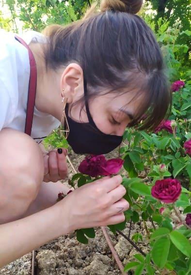 Moça de máscara preta cheirando uma flor roxa no Roseto di Santa Giustina, em Pádua
