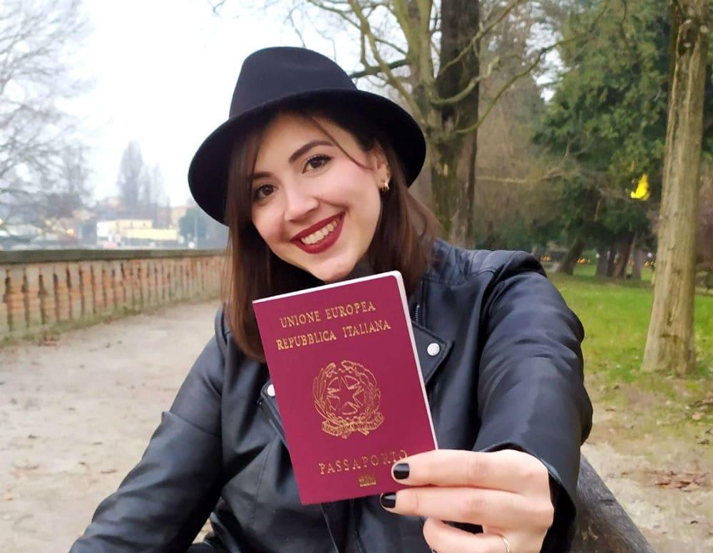 Mulher de chapéu segurando o passaporte italiano, cidadania italiana