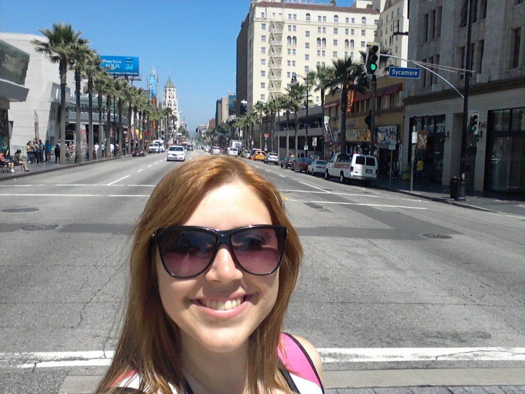 Selfie feita no meio da rua em Hollywood Boulevard, em Los Angeles. A rua está vazia, com alguns carros estacionados e algumas pessoas nas calçadas.