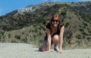 Foto de mulher agachada num chão de pedrinhas, com o letreiro de Hollywood no fundo, à esquerda