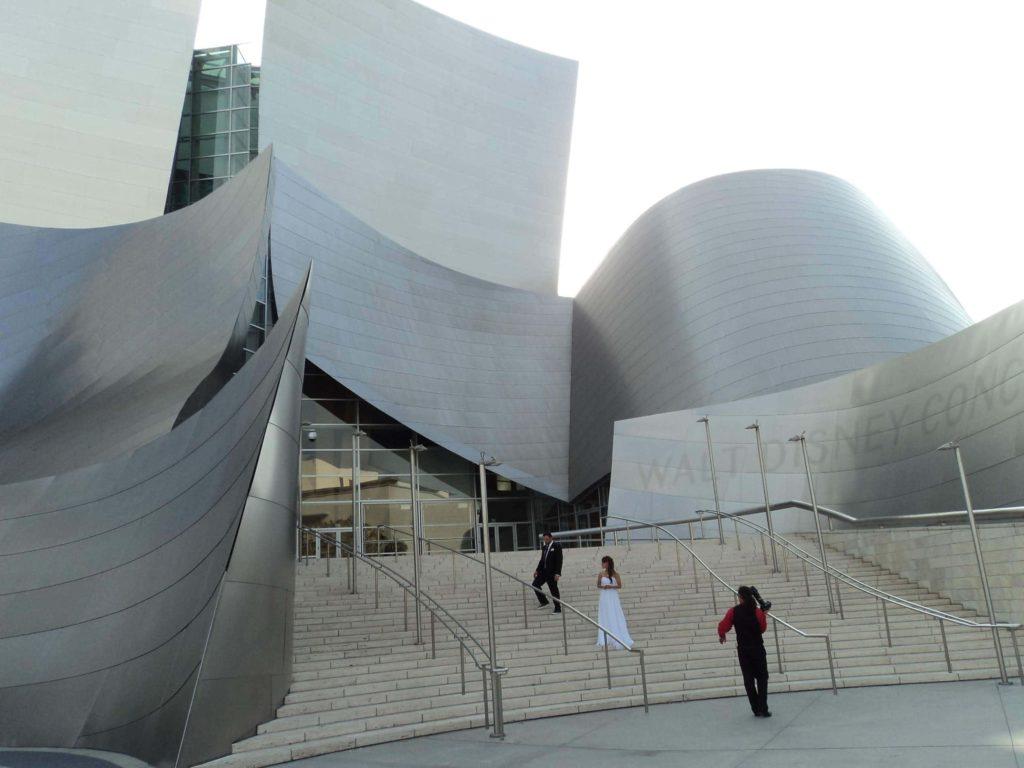 Fachada do Walt Disney Concert Hall em Los Angeles,com um casal de noivos e um fotógrafo nas escadas