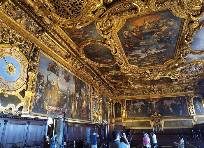 Foto aberta de uma sala com afrescos no teto e nas paredes com adornos dourados no Palazzo Ducale, em Veneza