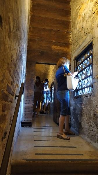 Foto de um corredor com paredes de pedra e uma porta estreita de madeira, duas janelas e algumas pessoas observando: o interior da Ponte dos Suspiros em Veneza