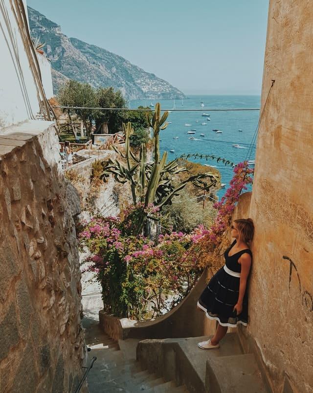 Foto de uma mulher encostada numa parede com o mar ao fundo em Positano, na Itália