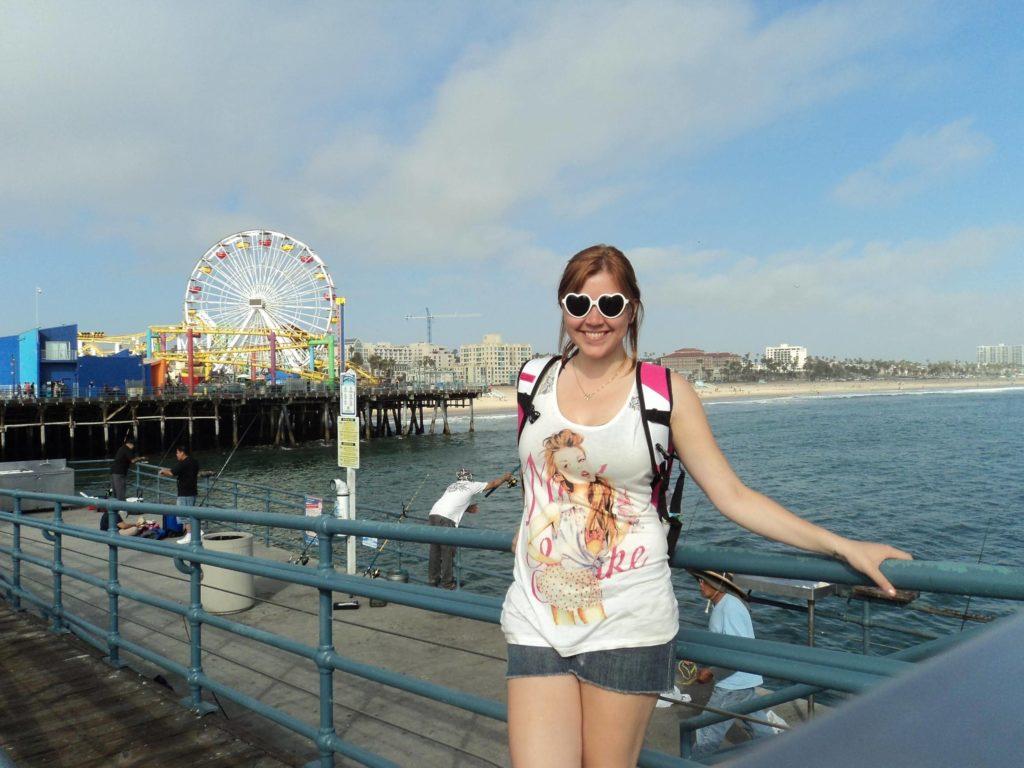Foto no pier de Santa Monica, com o parque de diversões ao fundo, em LA